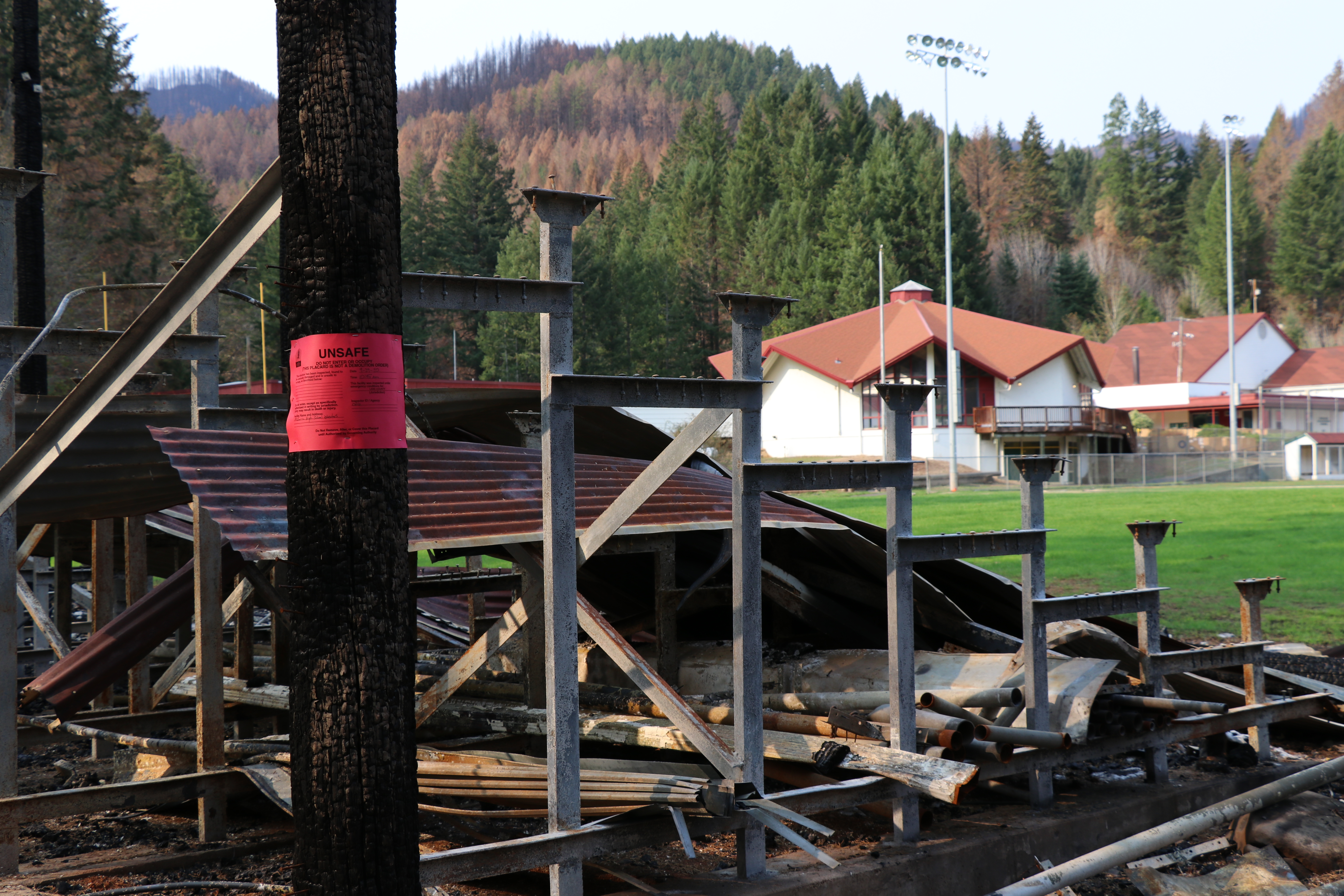 photo of charred bleachers, with school buildings in background